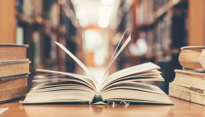 Ein geöffnetes Buch in der Mitte und mehrere geschlossene Bücher rechts und links davon. Bücherregal im Hintergrundn Büch